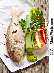 Fish - Fresh fish and fresh vegetables on a wooden board