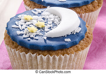 cupcake with blue icing and half moon and small yellow stars