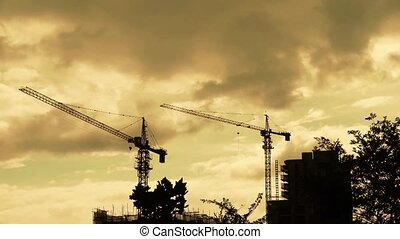 Construction-cranes,clouds cover sky,building...