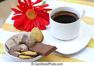 Cup of coffee with  desert and red gerbera