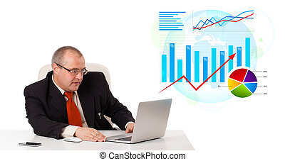 Businessman sitting at desk with laptop and statistics,...