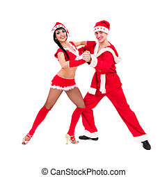 Happy young couple wearing santa claus clothes dancing...