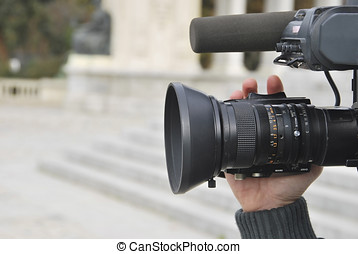 Video camera - A hand is operating a professional video...