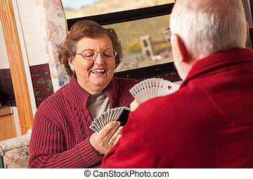 Happy Senior Adult Couple Playing Cards in Their Trailer RV...