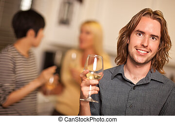 Smiling Young Man with Glass of Wine Socializing