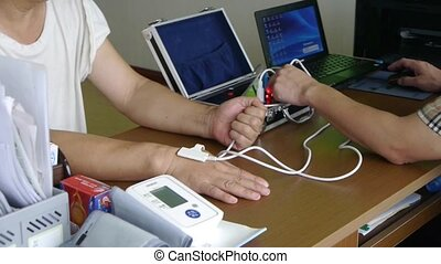 Doctor check blood pressure for patient use electronic...