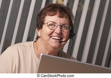 Smiling Senior Adult Woman with Telephone Headset and Monitor