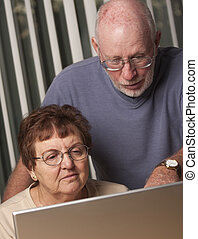 Smiling Senior Adult Couple Having Fun on the Computer