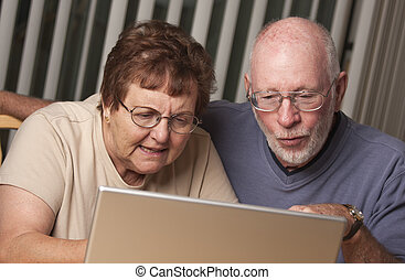 Smiling Senior Adult Couple Having Fun on the Computer...