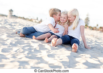 Adorable Sibling Children Kissing the Youngest at the Beach.