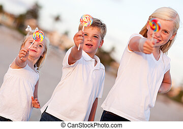 Cute Brother and Sisters Enjoying Their Lollipops Outside at...
