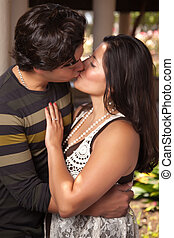 Attractive Hispanic Couple Kissing Outdoors