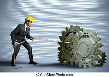 Businessman turning a gear system with rope