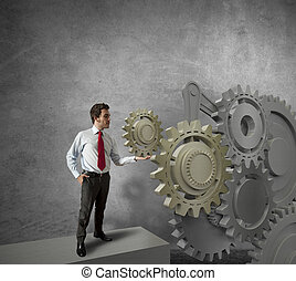 Businessman turning a gear system - Concept of a businessman...