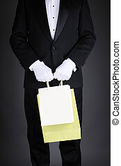 Man in Tuxedo with Gift Bags - Closeup of a gentleman in a...