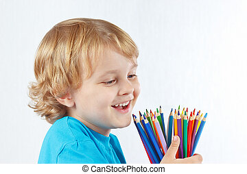 Little cute child with color pencils on a white background