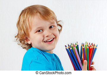 Smiling child with color pencils on a white background