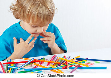 Little boy at the table with color pencils on a white...