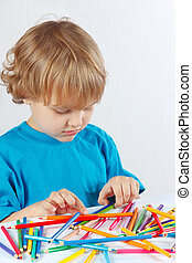 Young cute blond boy at the table with color pencils on a...