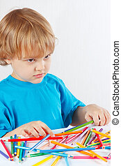 Young blond boy at the table with color pencils on a white...