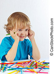 Young cute boy at the table with color pencils on a white...