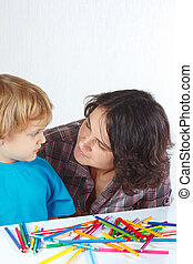 Little boy with his mother draws with color pencils on a...