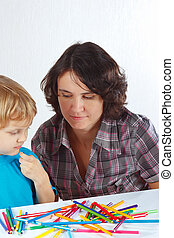 Little cute boy with his mother draws with color pencils on...