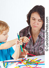 Young mother teaches her son to draw with color pencils on a...