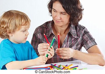 Young mother teaches her child to draw with color pencils on...