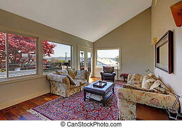 Large living room with two sofas and red rug.