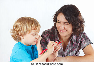 Mother teaches her child to draw with color pencils on a...