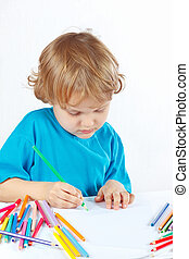 Little cute blond boy draws with color pencils on a white...