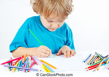 Little blond boy draws with color pencils on a white...