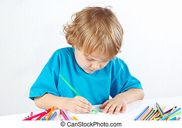 Little cute boy draws with color pencils on a white...