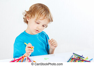 Young cute boy draws with color pencils on a white...