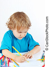 Little child draws with color pencils on a white background