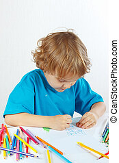 Cute child draws with color pencils on a white background