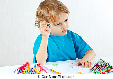 Little cute child draws with color pencils on a white...