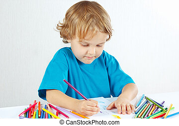 Little boy draws with color pencils on a white background