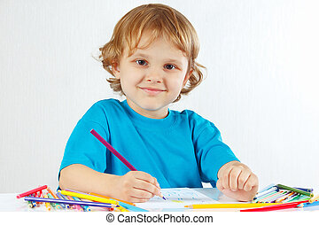 Little smiling boy draws with color pencils on a white...