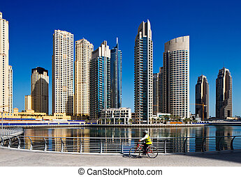 A cyclist cycles the Marina walk overlooking the Dubai...