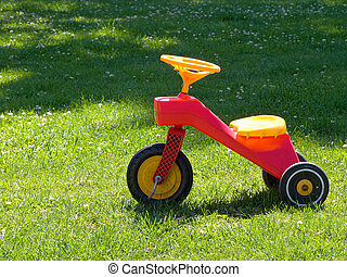 Tricycle on the grass - Bright colorful Tricycle standing on...