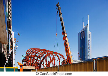 A mobile crane is holding the steel