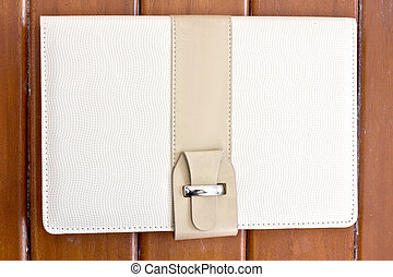 white leather cover of note book on wood