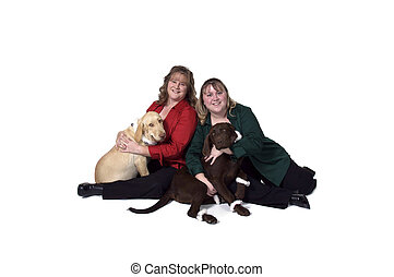 Two Women Posing With Their Labrador Retrievers