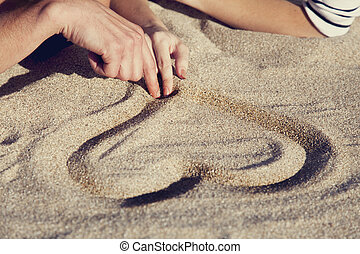 People drawing heart at sand