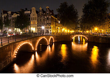Amsterdam bridges - Amsterdam canal at night with lights on...