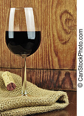 Glass and cork of fine italian red wine, wooden bacground