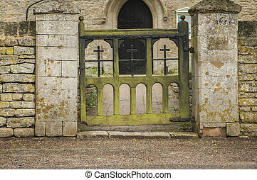 Old decaying wooden Church gate wuth green moss on