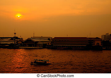 Long tail boat in Chaopraya river at sunset